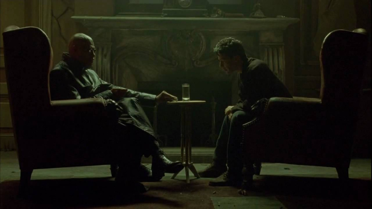Morpheus and Neo sitting across from each other in a dark room
