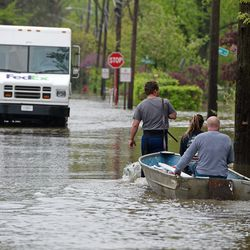 Triston Bakulinski pulls Lea Civitella and his dad Stanley Bakulinski along Hawthorne Lane in Des Plaines Monday as the neighborhood is flooded from Des Plaines River. They were hauling some pumping supplies to try and alleviate flooding in their homes.