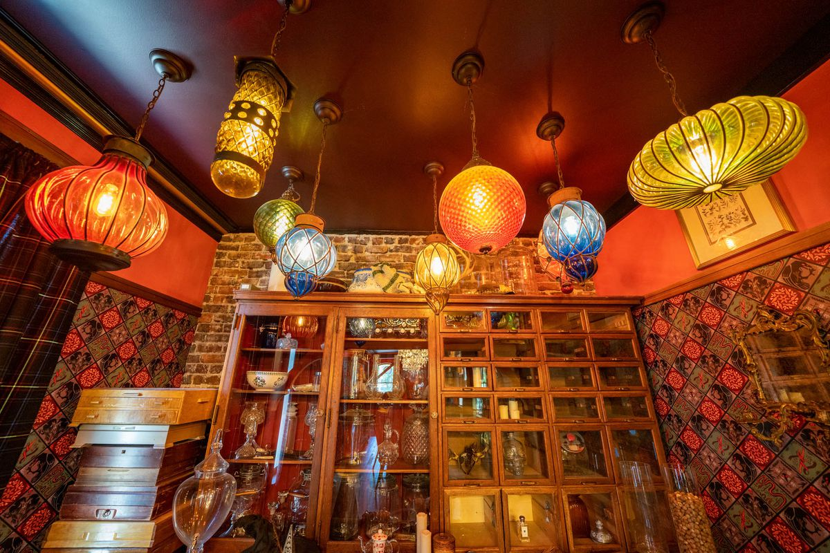 A variety of lighted yellow, orange, and blue lanterns and lamps hanging from the ceiling in a small room, decorated with a cabinet, wooden boxes, and colorful wallpaper.