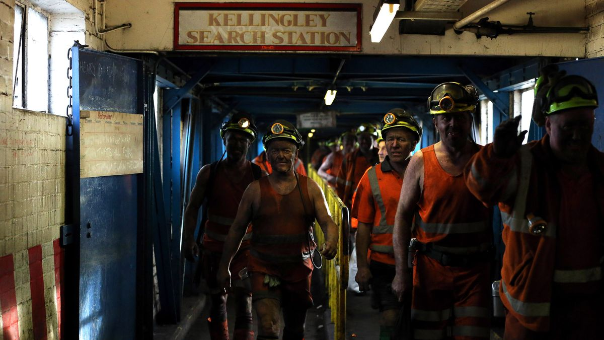 A group of miners in reflective clothing, wearing head lamps and celebratory expressions, leave the exit of an underground coal mine, sunlight coming in a window to the left.