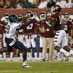 Temple's Vaughn Carraway (14) intercepts a pass intended for Villanova's Norman White (8) during the first half of an NCAA college football game on Friday, Aug. 31, 2012, in Philadelphia. Carraway ran the ball back for a touchdown.