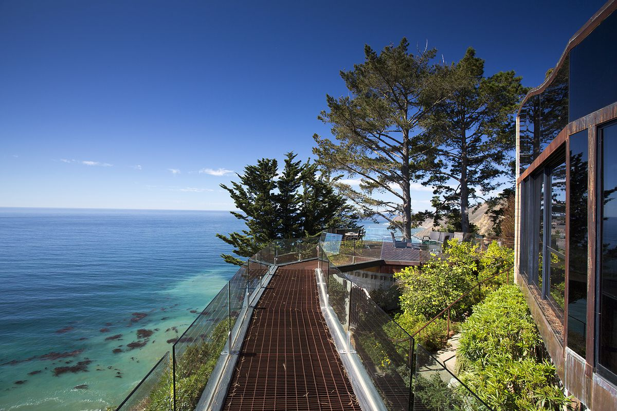 A bridge with glass walls sits high above the ocean. There are panoramic views and trees next to a house.
