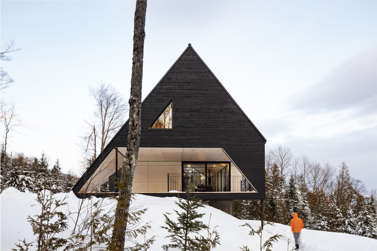 Charred timber A-frame cabin in the snow.