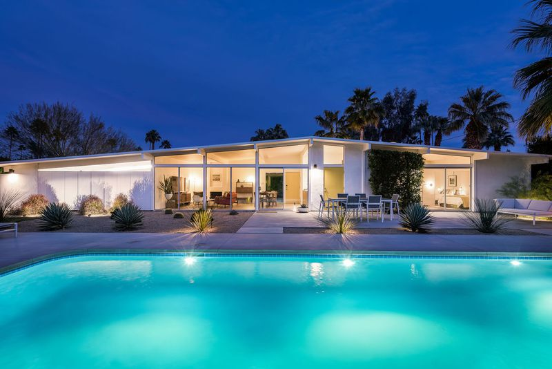 A white midcentury modern house with a low-slung roof sits in front of a turquoise pool at dusk.
