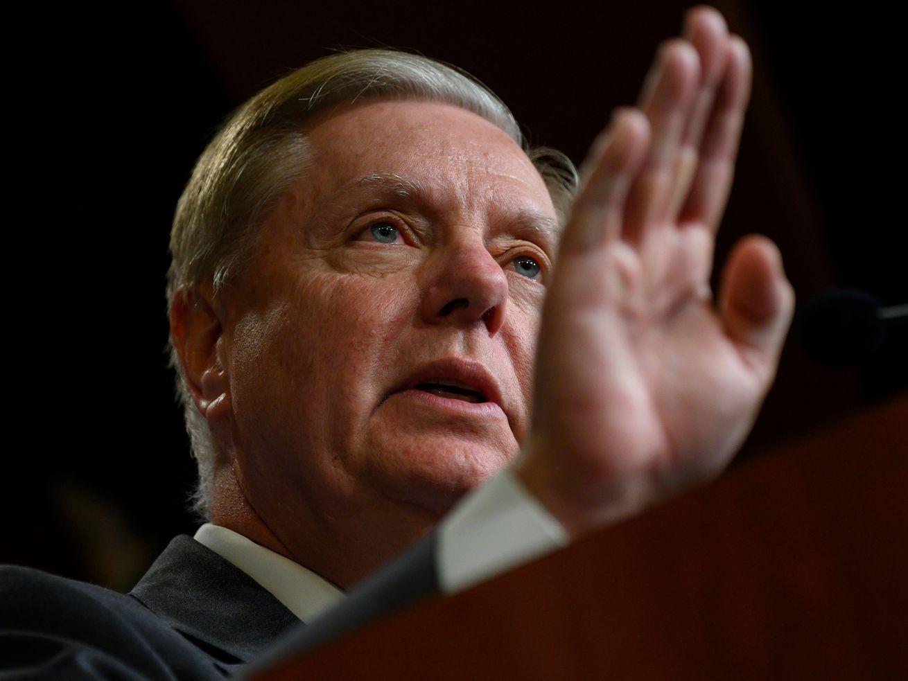 Senator Lindsey Graham holds up his hand while speaking.