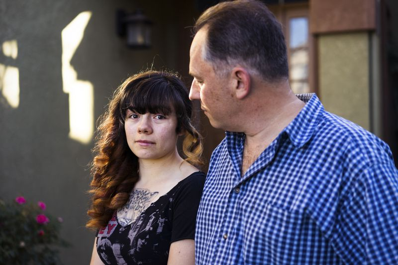 Emilie Cote with her father Michel outside their home in Gilroy, California.