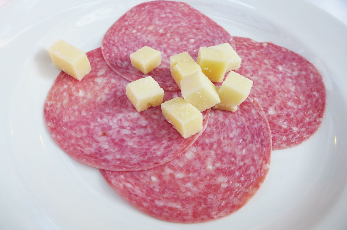 Pink slices of salami with cubed cheese on top.