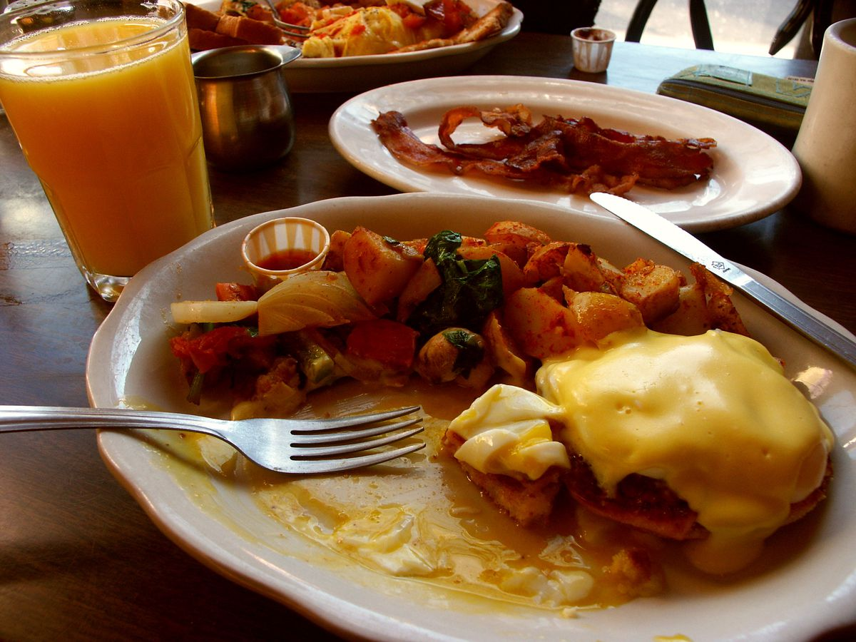 Closeup of a partially eaten eggs Benedict breakfast. A plate of bacon is visible in the background.