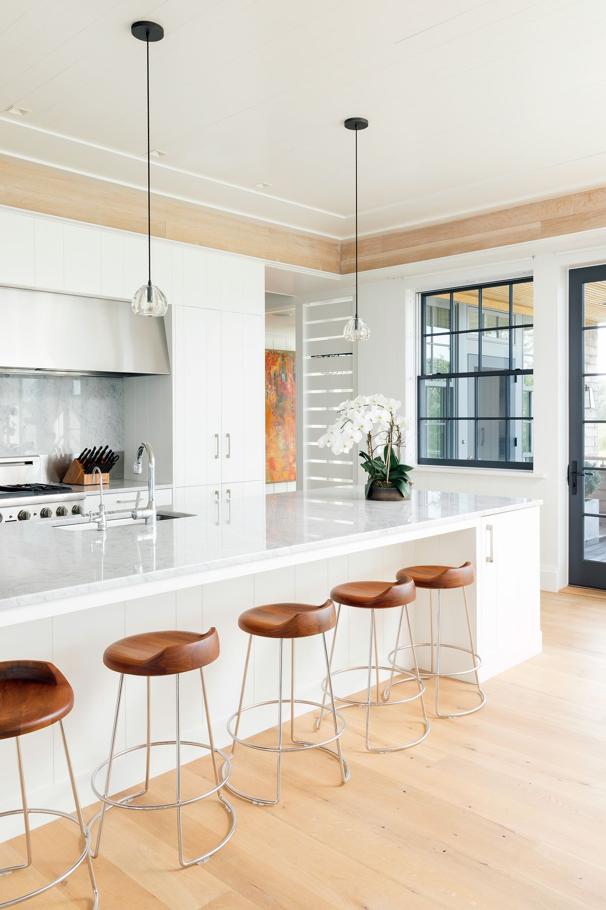 A white kitchen with a band of natural wood along the crown molding features a generous eat-in island.