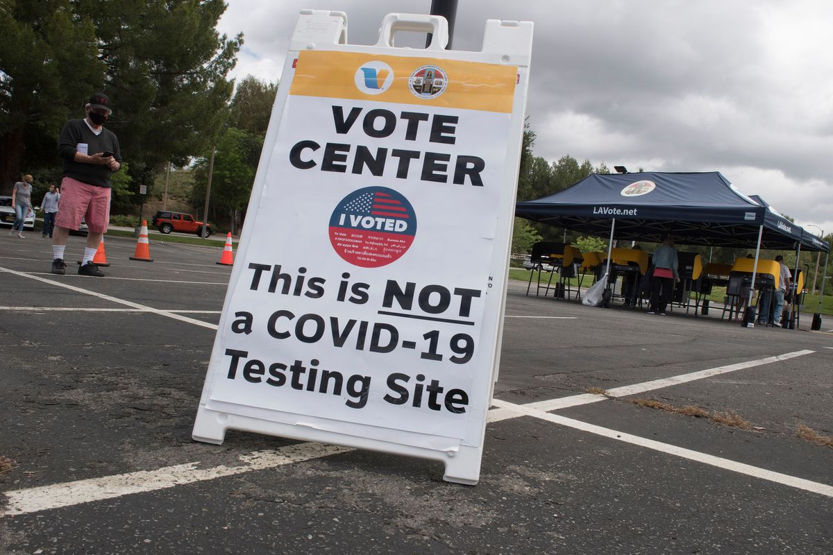 """A sign in a parking lot reads, """"Vote center. This is not a Covid-19 testing site."""""""
