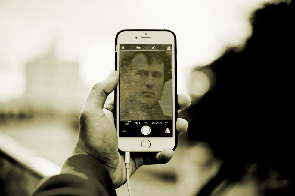 A man holds an iPhone to take what looks like a selfie but is actually a vintage-looking photograph.