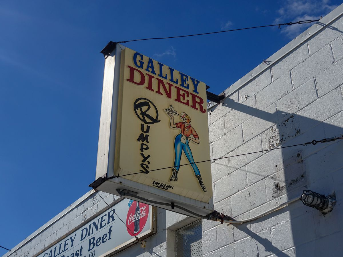 """Exterior of a diner, featuring a white brick wall. Old-fashioned signage reads """"Galley Diner"""" and """"Rumpy's,"""" with an image of a woman holding a tray of food."""