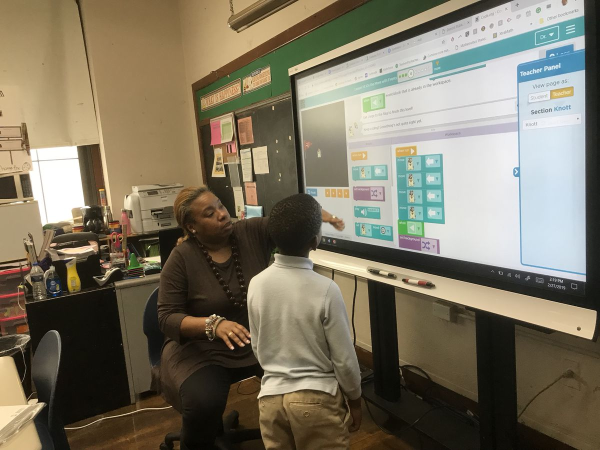 Dorian Roberts, a teacher at Bagley Elementary School of Journalism and Technology, works with students on coding during a recent class.