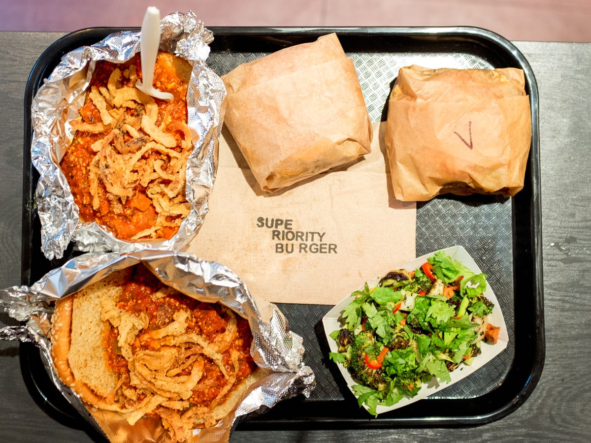 A black plastic tray has five pieces of food, including two in foil, a paper tray of salad, and two brown paper-wrapped burgers.