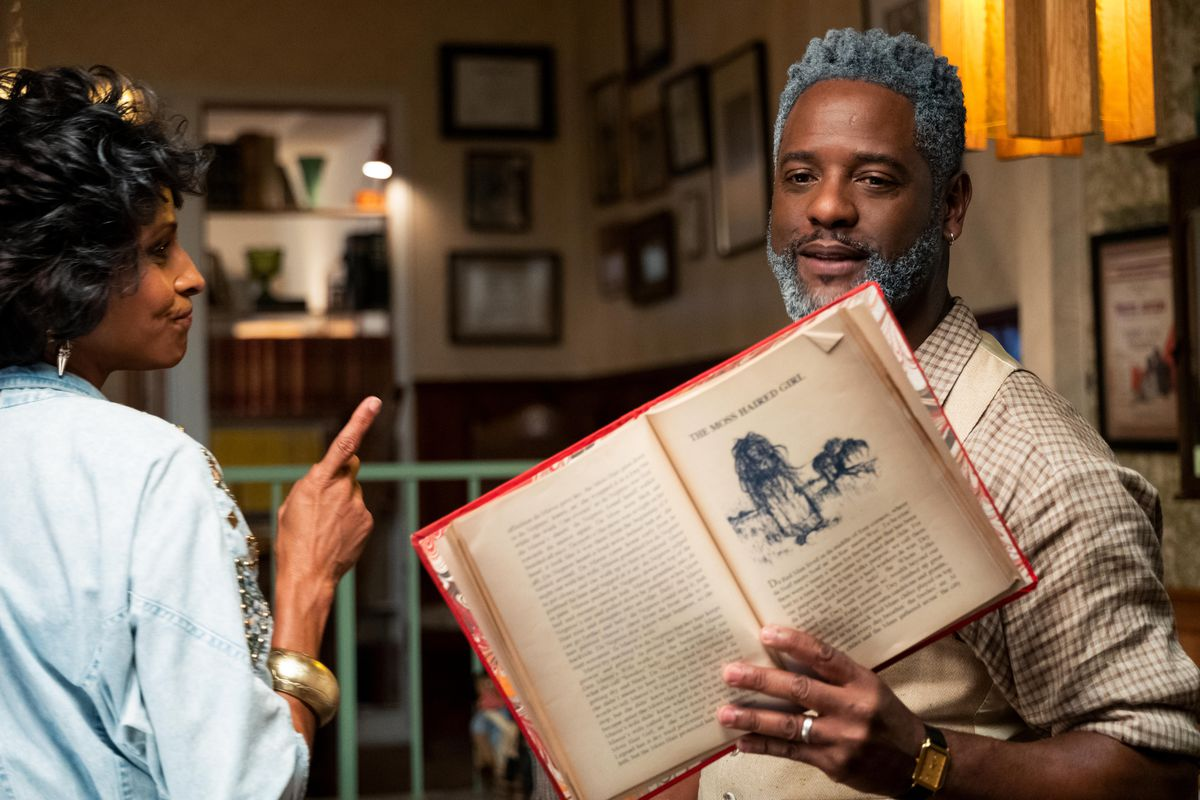 Amos (Blair Underwood) holds up a book of African folklore displaying a monster called The Moss Haired Girl in Bad Hair