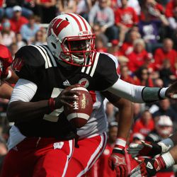 Quarterback D.J. Gillins is corralled by defenders.