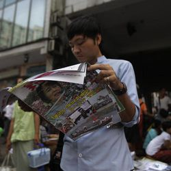 A Myanmar man reads a newspaper featuring pro-democracy leader Aung San Suu Kyi, a day after landmark by-elections in Yangon, Myanmar, Monday, April 2, 2012. Suu Kyi, 66, was elected to parliament Sunday in a historic victory buffeted by the jubilant cheers of supporters who hope her triumph will mark a major turning point in a nation still emerging from a ruthless era of military rule.