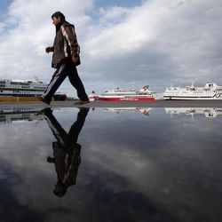 A man walks past a puddle at Piraeus port near Athens during a 48-hours strike at the port of Piraeus, near Athens, on Tuesday, April 10, 2012.  Ferry services to Greek islands have been halted by a 48-hour strike that is expected to hit the start of the country's tourism season and celebrations for Orthodox Easter.