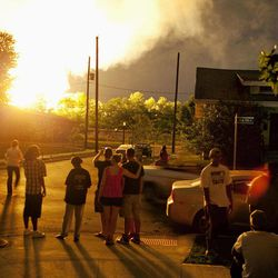FILE - In this July 11, 2012 file photo, people watch flames shoot up from a freight train that derailed and some cars burst into flames in Columbus Ohio. The accident prompted the evacuation of a mile-wide area as firefighters and hazardous materials crews monitored the blaze. For two decades, one of the nation's most common types of rail tankers, known as a DOT-111s, have been allowed to haul hazardous liquids from coast to coast even though transportation officials were aware of a dangerous design flaw that almost guarantees the car will tear open in an accident. The rail and chemical industries have committed to a safer design for new tankers, but they do not want to modify tens of thousands of existing cars. That's despite a spike in the number of accidents.