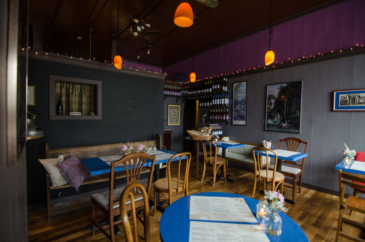 Interior of a dimly lit small restaurant with light wooden floor, gray walls with purple trim near the ceiling, string lights, and tables with bright blue tops.