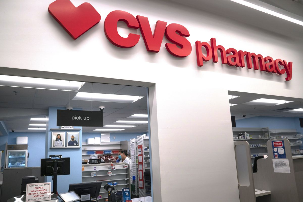 In this March 17, 2020, file photo, Pharmacist Evelyn Kim, wears a mask and gloves at the CVS pharmacy at Target in the Tenleytown area of Washington.