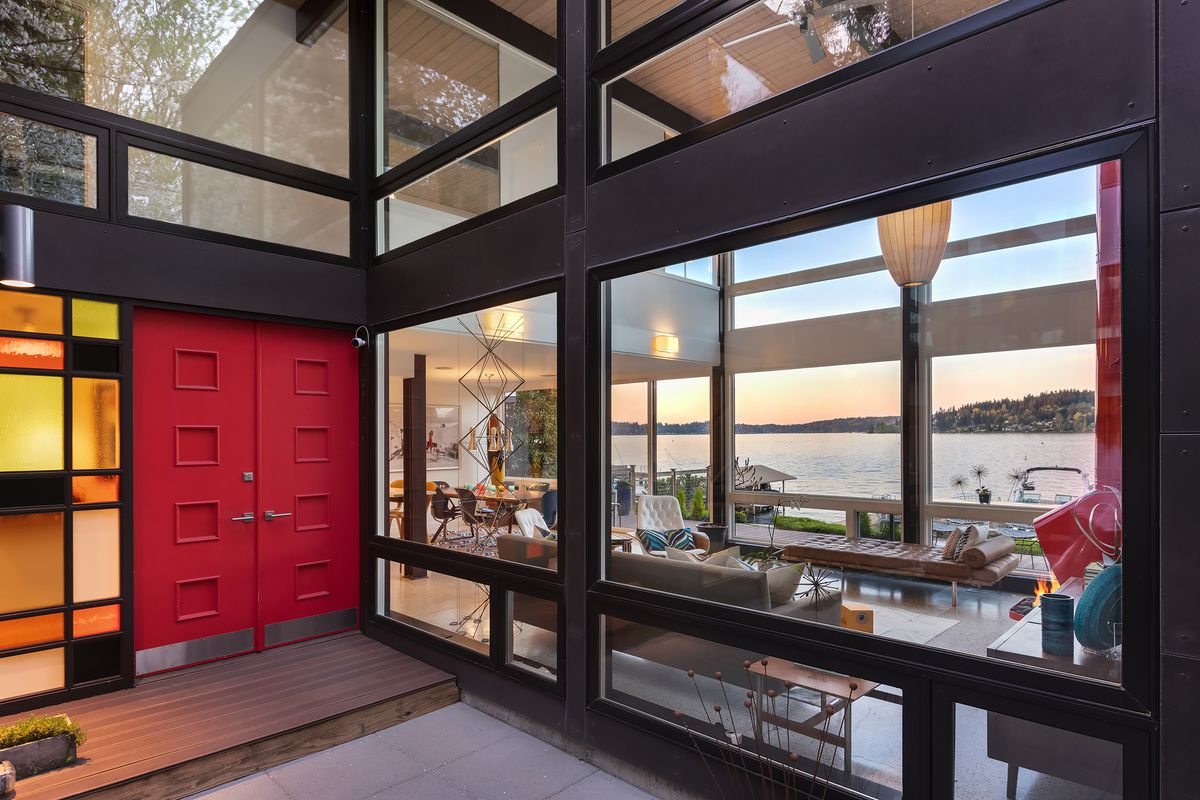 The entrance to a glass and steel home has a bright orange red door with stained glass next to it.