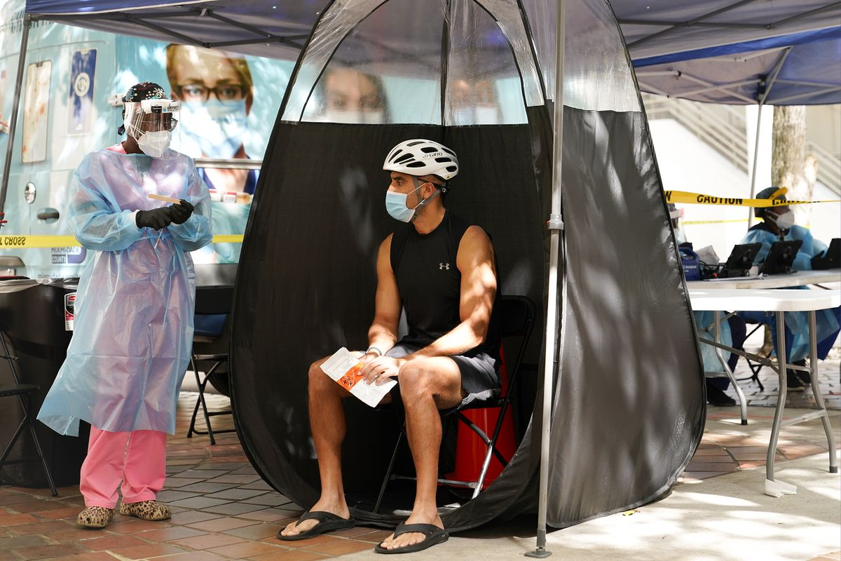 A person sits in an outdoor Covid-19 testing facility talking to a nurse wearing a face shield, mask, gown, and gloves.