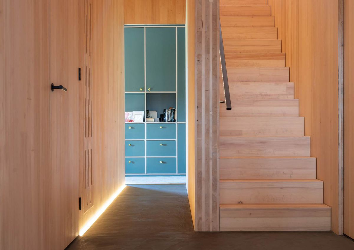 Timber stairs leading to a second level, while down a hallway you can see teal built-in cabinetry with white trim.