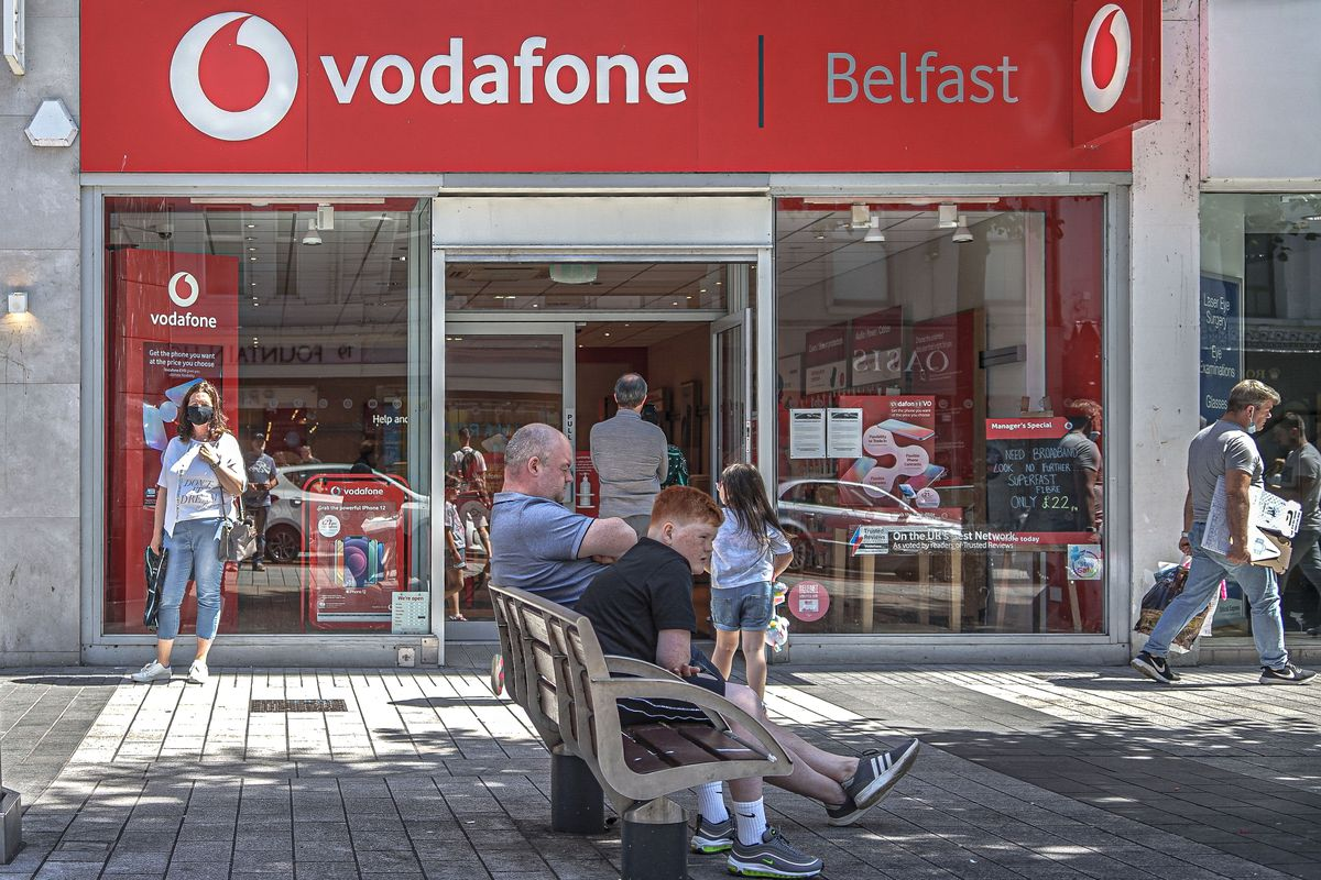 Masked customers queue to enter Vodafone Mobile Phone Store...