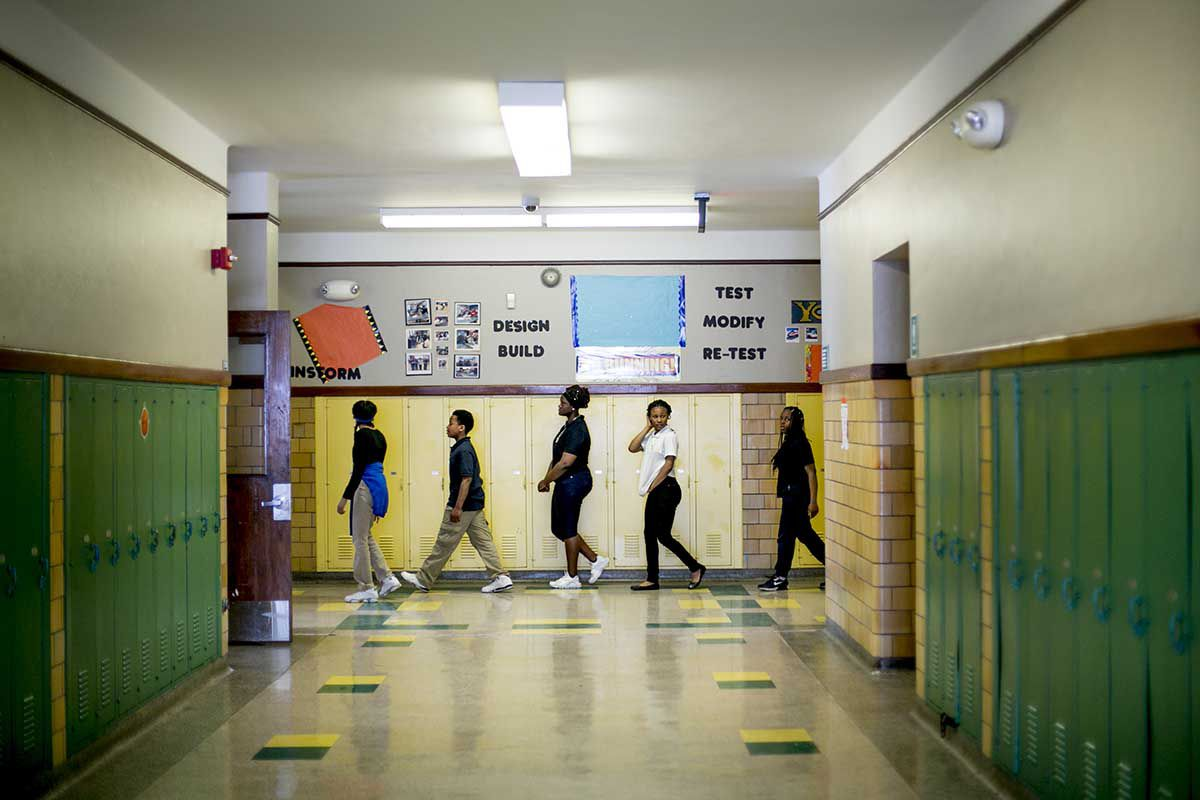 Students walk down a hallway during class change. The walls are lined with green and yellow lockers.
