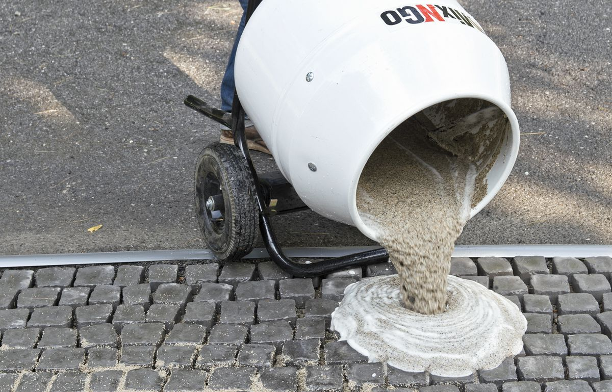 Man Pours Grout On Cobblestone Driveway Apron
