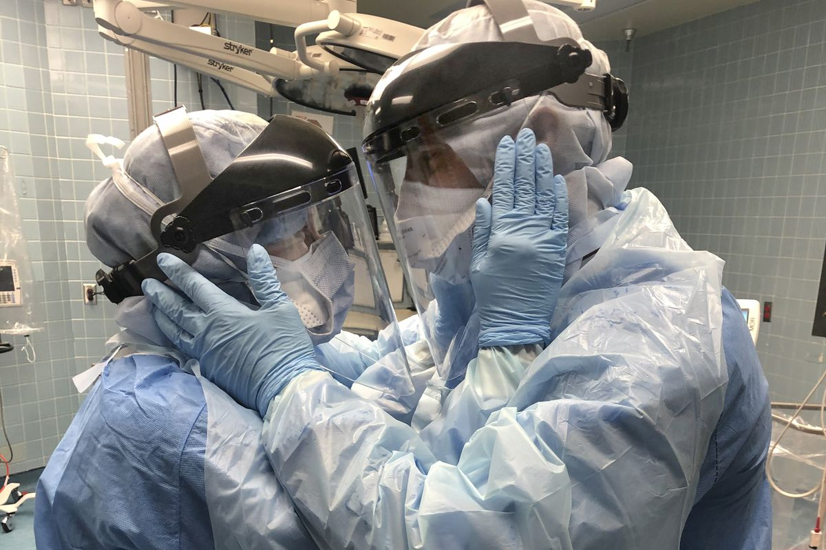 """In this March 30, 2020, photo from Tampa General Hospital in Florida, two nurses wearing protective equipment look into each other's eyes. """"The Angels braved the storm,"""" John W. Fountain writes in a poetic tribute to medical workers. """"Fought on — wearied and worn. Their souls forever torn. By the ones they lost. And by the ones they won."""""""