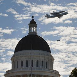 Space Shuttle Endeavour mounted on NASA's Shuttle Carrier Aircraft, passes over the California state Capitol, Friday, Sept. 21, 2012,  in Sacramento, Calif. Endeavour is making a final trek across the country to the California Science Center in Los Angeles, where it will be permanently displayed.