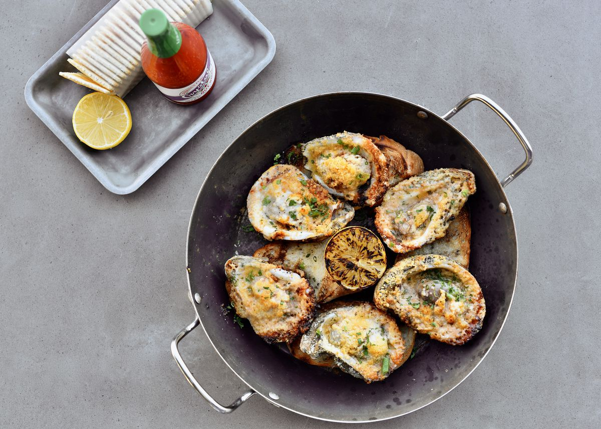 A skillet is filled with oysters on the half shell, grilled and served with charred lemon. Hot sauce, lemon, and crackers sit on a silver tray to the left.