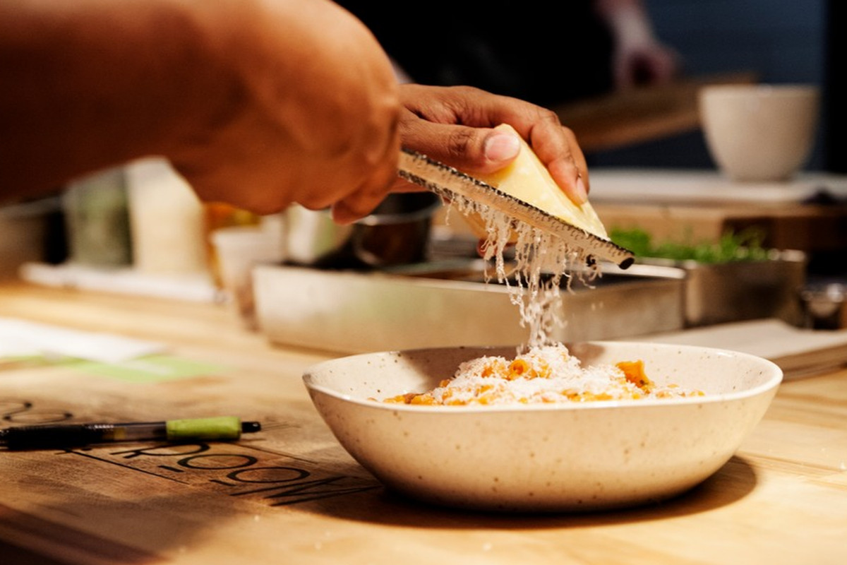 A bowl of pasta gets cheese grated over it at The Dough Room