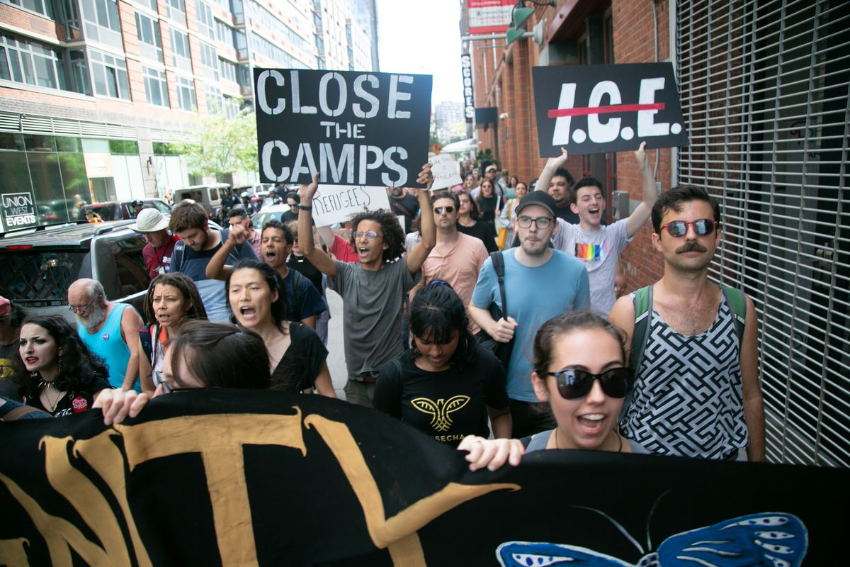 "Protestors against US immigration policies like child detention march down a street holding signs like ""Close the Camps."""