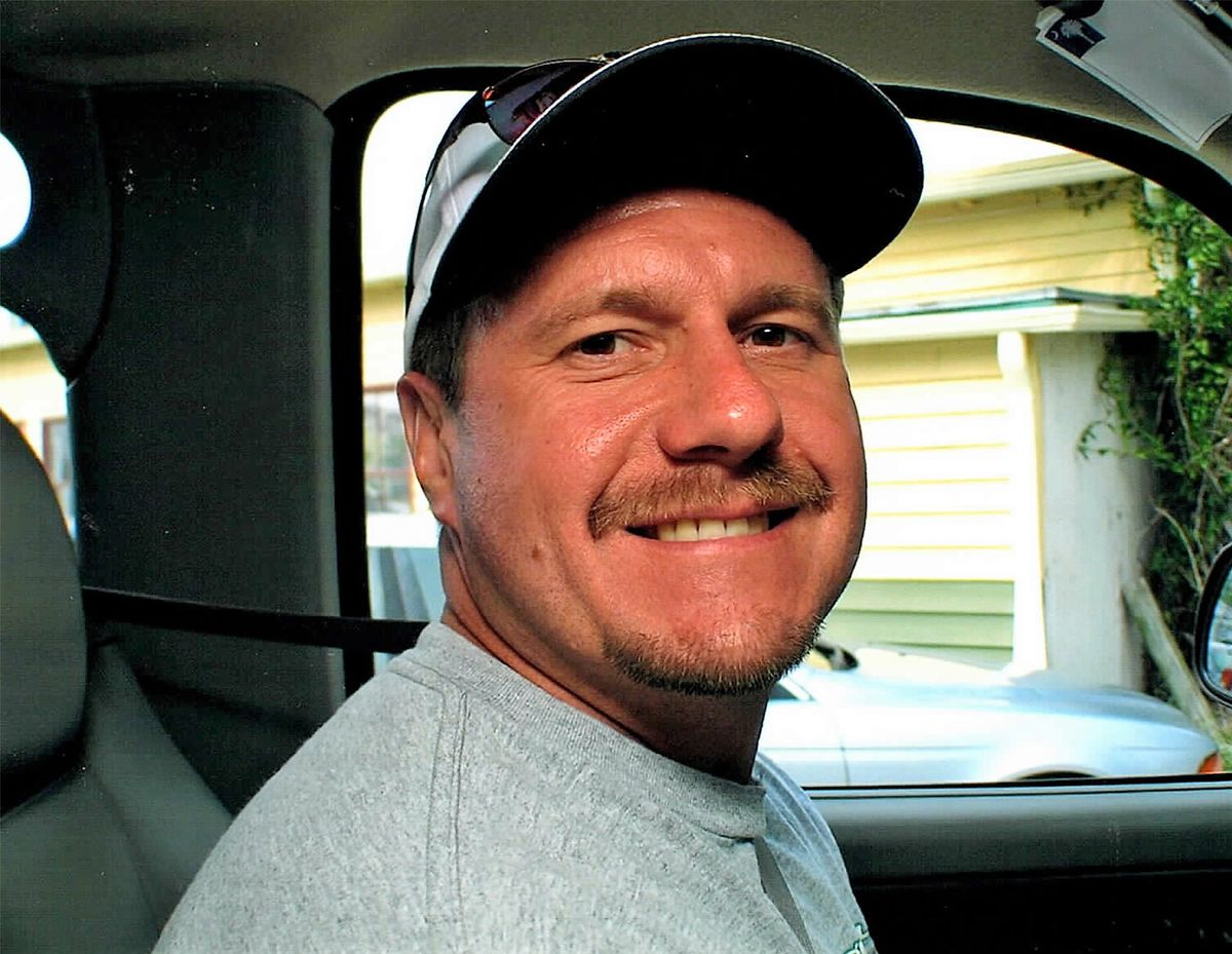 Smiling man wearing baseball cap in the front seat of his car.