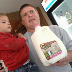 In this Sept. 21, 2012 photo, Matt Kilgus holds his two year-old son, Collin, along with a freshly produced gallon of milk bottled that day at the Kilgus Farmstead in rural Fairbury, Ill. Kilgus Farmstead is a family-run business that not only provides dairy products to central Illinois customers but are feeding a growing demand from the Chicago market for local and sustainable food and crops.