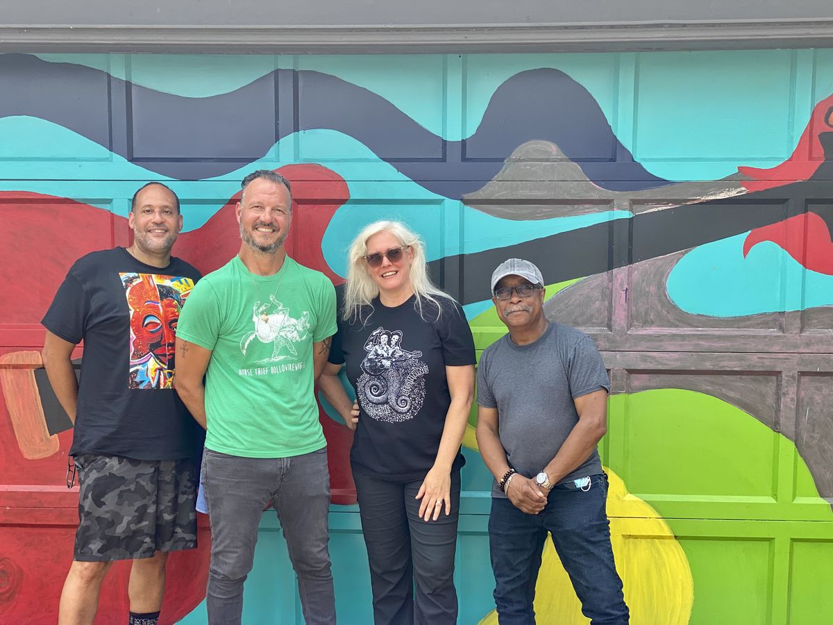 """Artist Paul Branton (left) with owner Paul Kostopanagiotou at Nicky's of Beverly, Sal Campbell of the Beverly Area Arts Alliance and fellow artist Phil Cotton in front of Cotton's mural dedicated to """"Lucille."""""""