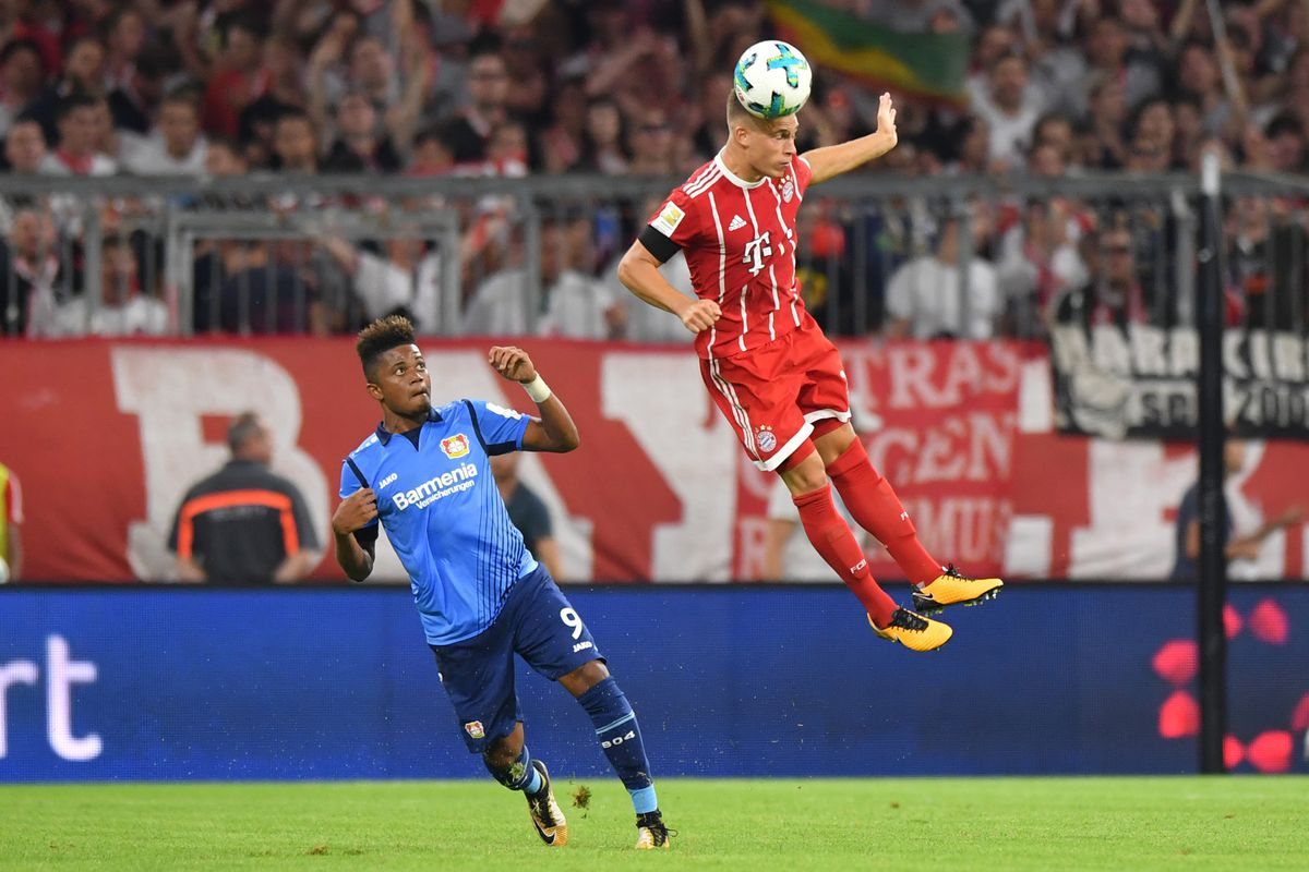 MUNICH, GERMANY - AUGUST 18: Joshua Kimmich of FC Bayern Muenchen goes for a header as Leon Bailey of Bayer Leverkusen watches during the Bundesliga match between FC Bayern Muenchen and Bayer 04 Leverkusen at Allianz Arena on August 18, 2017 in Munich, Germany.