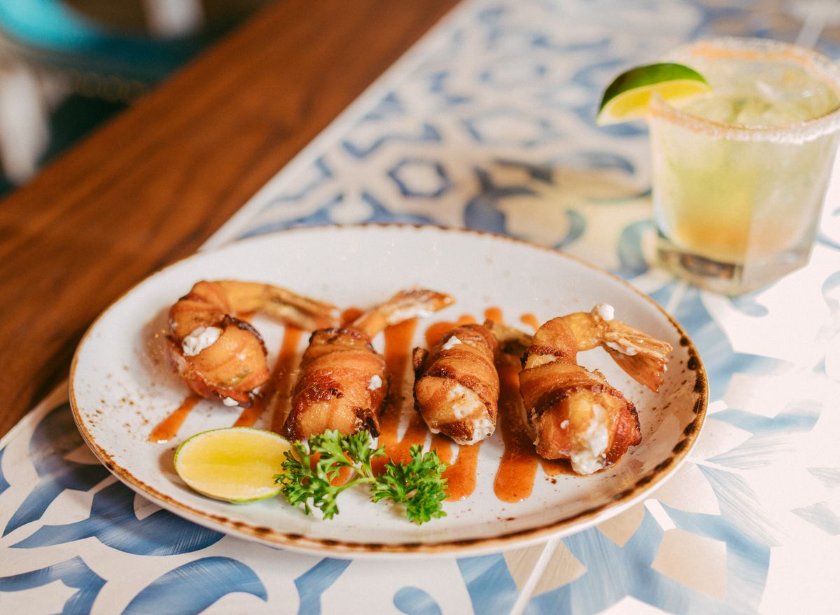 Place of bacon-wrapped shrimp and a margarita on the bar at Karina's Cantina