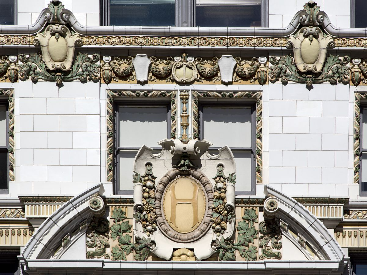 The exterior of the Hearst Building in San Francisco. There are elaborate design flourishes on the front of the building.