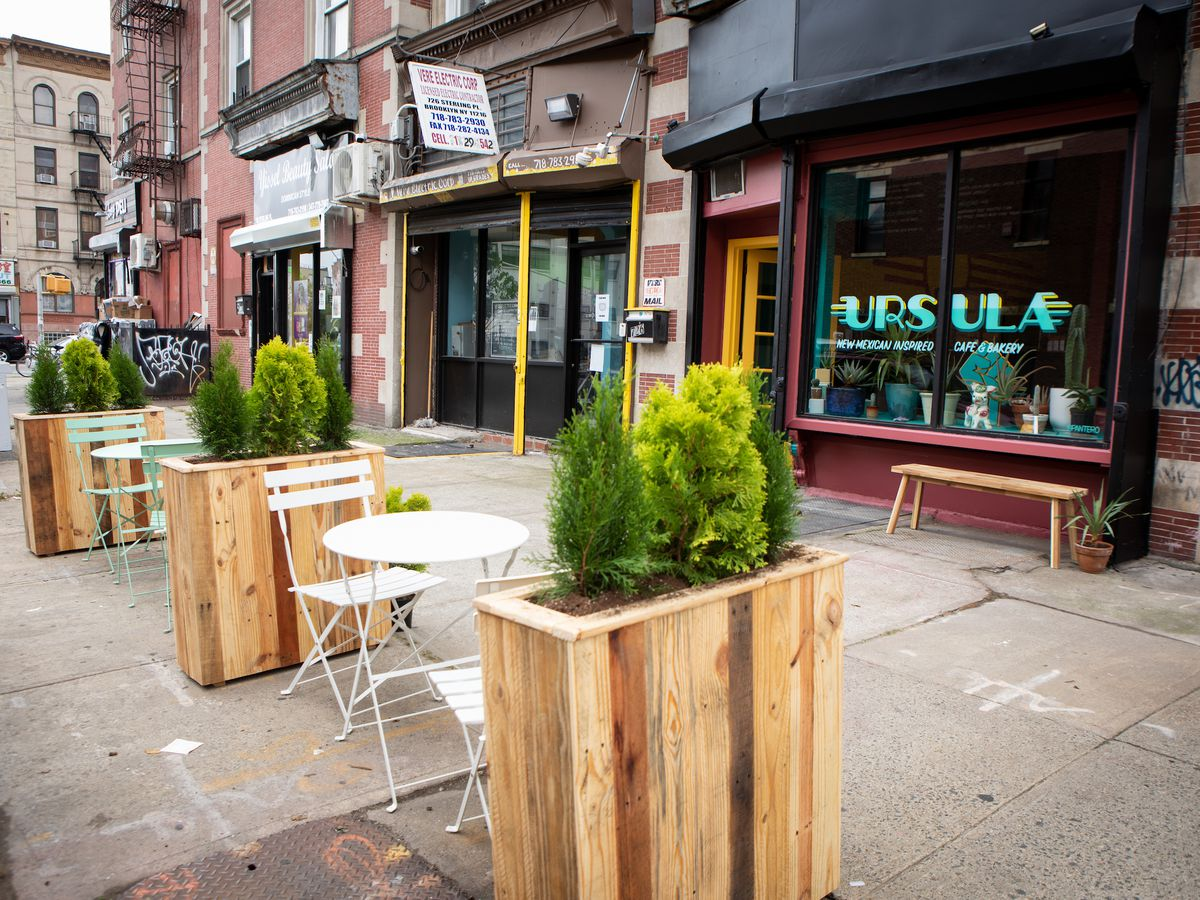 A few tables and chairs placed outside a restaurant along with some planter boxes
