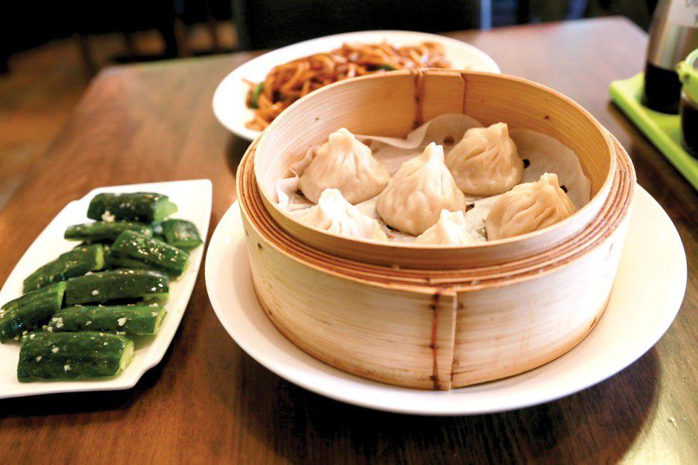 A steamer basket of soup dumplings, beside a plate of cucumbers on a wooden table