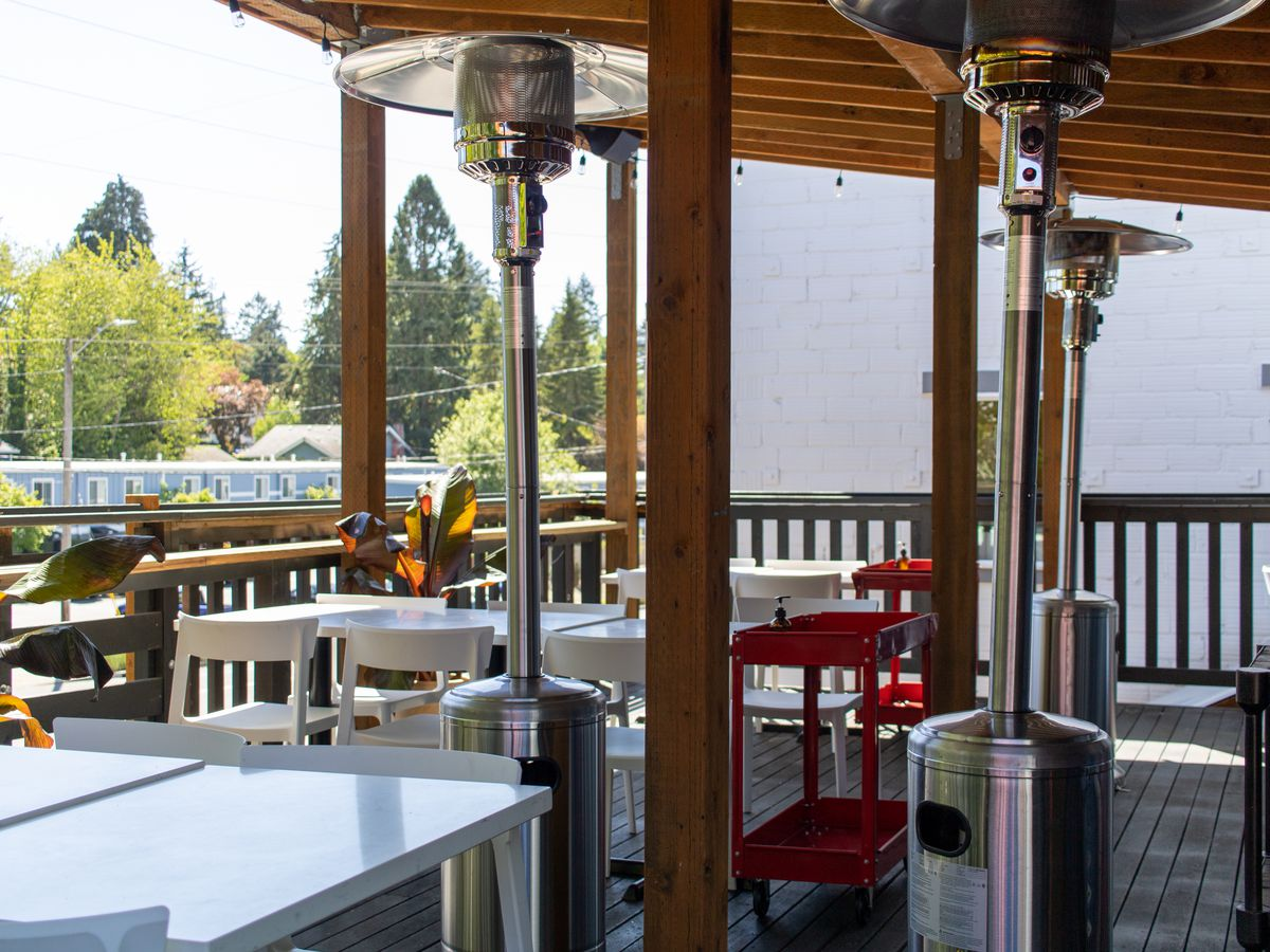 White metal tables and chairs sit on a covered wooden deck.