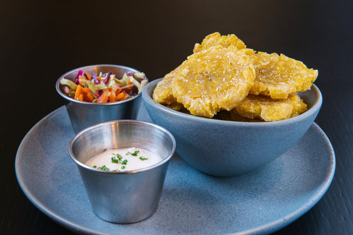 Light blue bowl of tostones sits on a matching plate. On the plate, there are two small metal cups — one with an aioli and the other with pikliz. The plate and bowl sit isolated on a black background.
