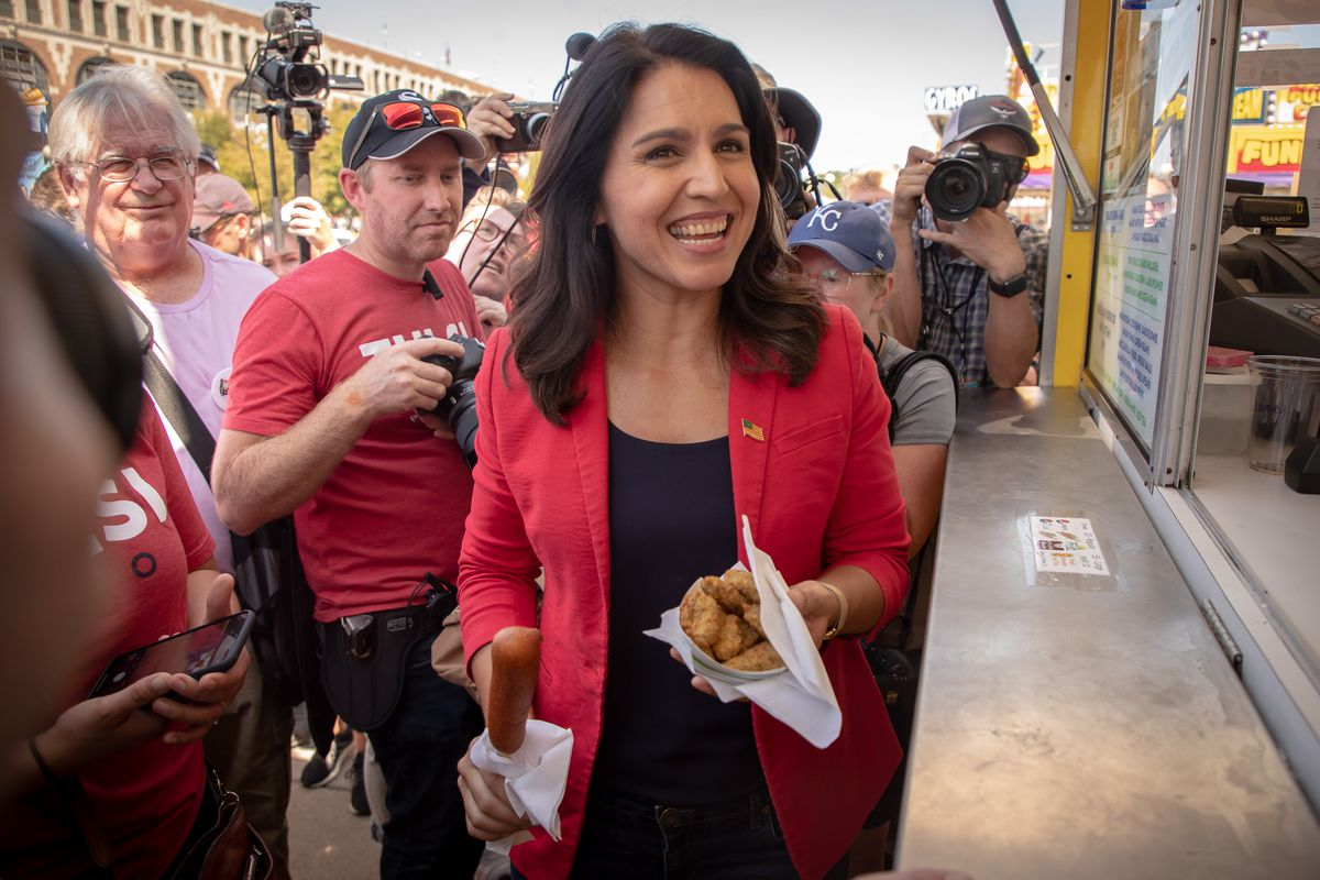 Tulsi Gabbard holds a basket of fried avocado slices in front of a food stand