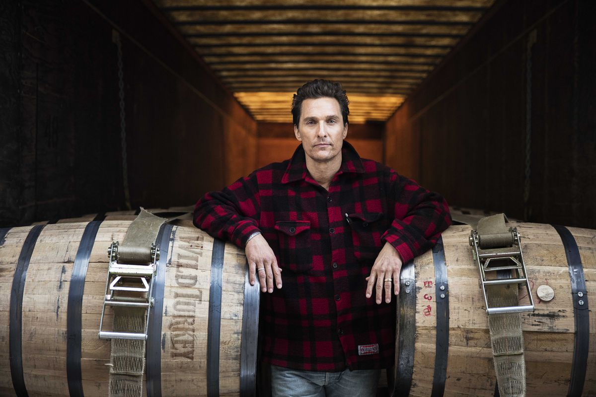 Matthew McConaughey poses with Wild Turkey bourbon barrels