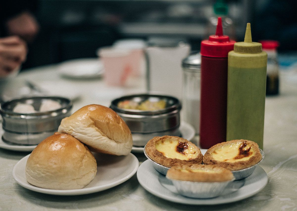 Barbecue pork buns, egg tarts, dim sum, and condiments on a table.