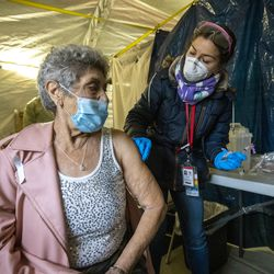 Kelsey Merlo, a pharmacy intern and a University of Utah pharmacy student, right, prepares to give Maria Chavez a COVID-19 vaccination at the Fourth Street Clinic in Salt Lake Cityon Tuesday, Jan. 26, 2021. The Salt Lake County Health Department allocated 80 doses of the vaccine to the clinic, which serves many people experiencing homelessness.